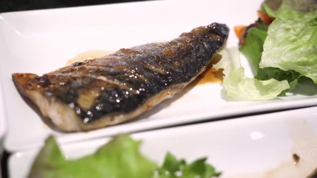 4k närbild grillad saba fisk, japansk recept meny, lunchtid, asiatisk mat, kost kost, omega 3, fluorescerande ljus, grön gröngröngrön, måltidskurs middag, inomhus restaurang, pan ner rörelse - misosås bildbanksvideor och videomaterial från bakom kulisserna