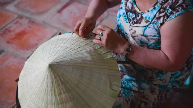 4k närbild film av handen att göra vietnamesiska hatten - halmslöjd bildbanksvideor och videomaterial från bakom kulisserna