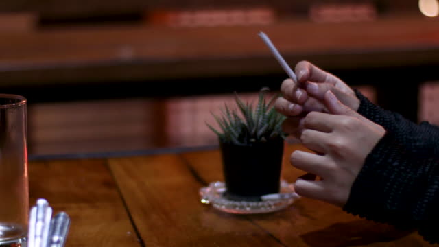 4k close up young Asian female hand holding cigarette wearing black long sleeves sweater, lonely mood, stressful anxiety, worry, night, evening scene, warm light, close up, thoughtful, wood table
