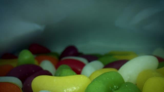 vídeos de stock e filmes b-roll de 4k close-up bug eye view inside jelly beans sweets pack - going inside eye