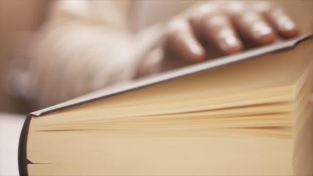 4k Close-Up Of A Hand Closing A Book - Slow Motion - Literature, Reading Slow Motion shot of a woman's hand closing a book. Perfectly usable for topics related to reading in general, reaching the end of something, studying, literature or education. textbook stock videos & royalty-free footage