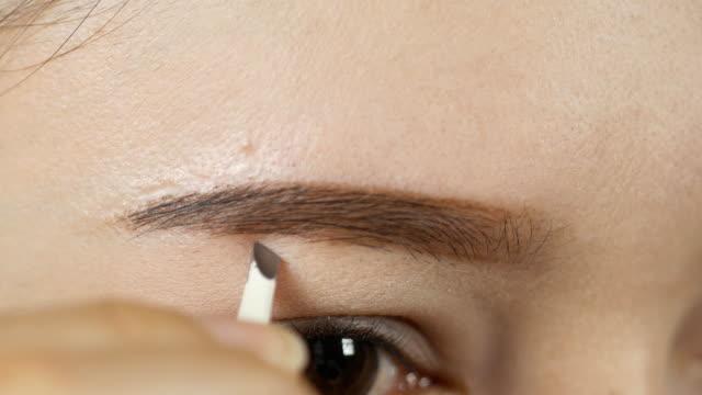 vídeos de stock e filmes b-roll de 4k closeup of a woman making a shape eyebrows with tweezers - sobrancelha