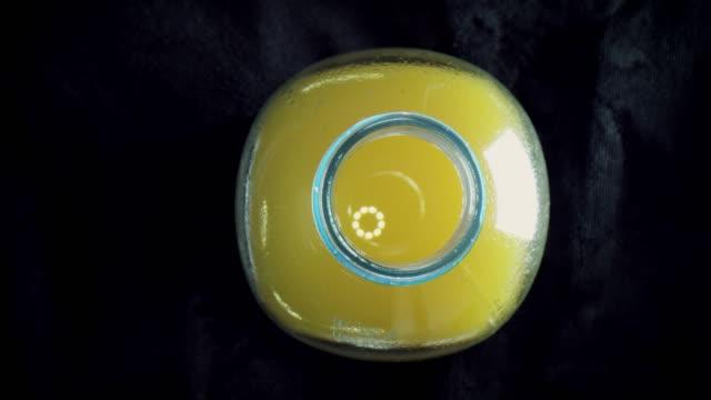 vídeos de stock e filmes b-roll de 4k close-up zoom in an orange juice bottle - going inside eye