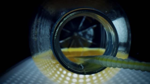 vídeos de stock e filmes b-roll de 4k close-up zoom in an orange juice bottle with straw - going inside eye