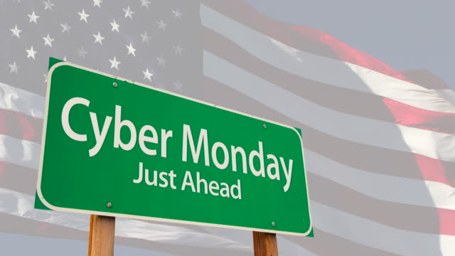 4k cyber monday green road sign over ghosted american flag - cyber monday стоковые видео и кадры b-roll