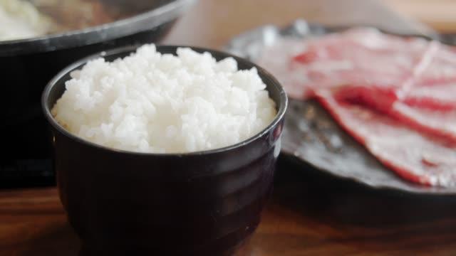 4k dci fußmaterial von japanischem reis und scheiben rindfleisch für die herstellung einer sukiyaki - reis grundnahrungsmittel stock-videos und b-roll-filmmaterial