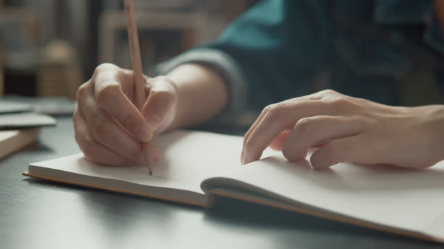 4k Dci Resolution asian woman sitting in living room while writing article for her freelance job. young girl writing her life planning on notebook , education ,learning ,inspiration concept