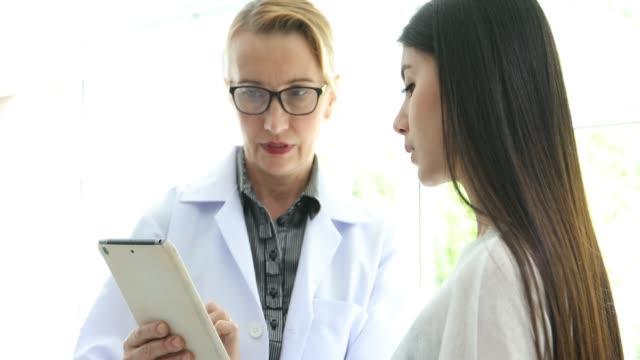 vídeos y material grabado en eventos de stock de 4 k doctor reunión y explicando la medicación al paciente de la mujer en su oficina en los hospitales - abrigo