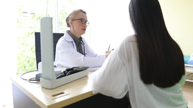 4k Doctor meeting and explaining medication to woman patient in his office at Hospitals