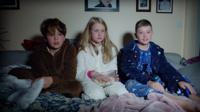 4k Dolly Shot of Children Watching Scary Movie on TV video