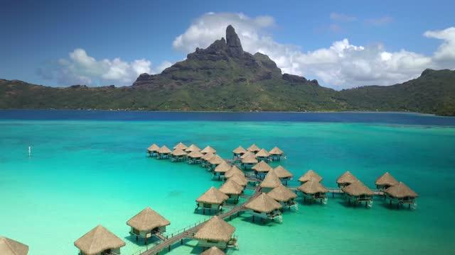 4k drone Bora Bora Tahiti. Aerial view of overwater bungalow villas in lagoon