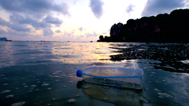 vídeos de stock e filmes b-roll de 4k: environmental pollution, bottle on the sea in sunset - beira d'água