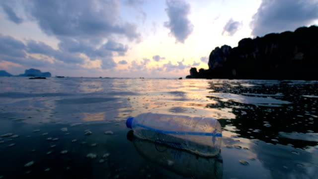 4k: Environmental Pollution, Bottle on the sea in sunset Plastic bottle with message brought to shore by sea waves bottle stock videos & royalty-free footage