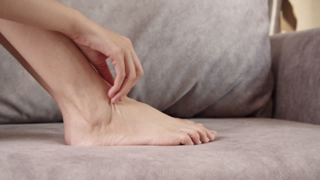 4k footage Close up shot asian woman scratching on her feet at home. Healthcare and medical concept