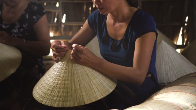 4k footage low light scene closeup of vietnamese craftsman making the traditional vietnam hat in the old traditional house in ap thoi phuoc village, cantho province, vietnam, traditional artist concept - tradycja filmów i materiałów b-roll