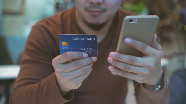 4k 亞洲男子在百貨公司合作空間使用信用卡和手機進行網上購物現金的畫面場景, 科技錢錢包和線上支付概念, 信用卡模型 - 銀包 個影片檔及 b 捲影像