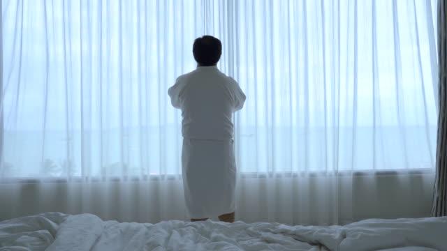 vidéos et rushes de 4 scène de séquences k d'asiatique homme marchant pour ouvrir le rideau sur les fenêtres et s'étirer le matin quand vous réveillez dans le concept d'hôtel de luxe chambre, style de vie et loisirs - peignoir