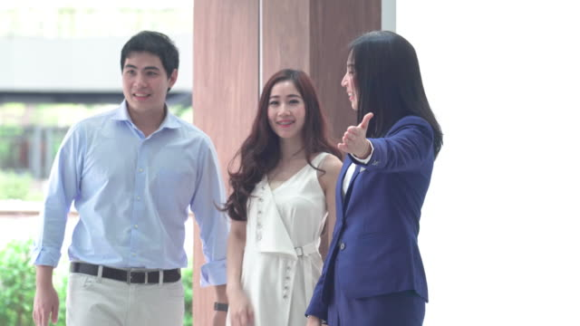 4k footage scene of Asian Saleswoman welcoming the couple customer in showroom