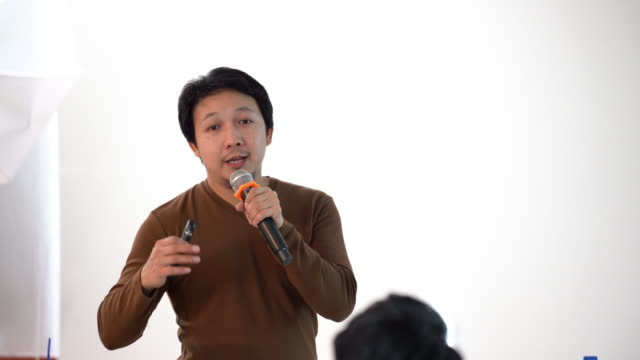 vídeos de stock e filmes b-roll de 4k footage scene of asian speaker with casual suit on the stage in front of the room presenting in the conference hall or seminar meeting room, business and education concept - training