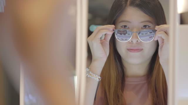 4k footage scene of Asian woman choosing sunglasses at store