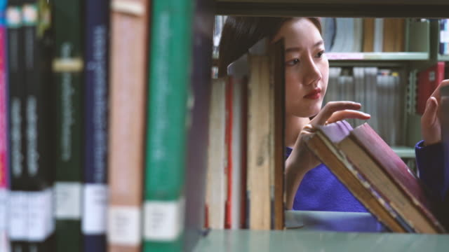 4k footage scene of Asian woman searching the book in library