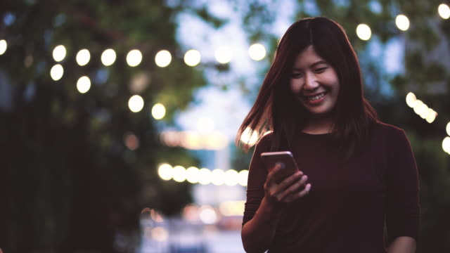 4k footage scene of attractive Asian woman using smartphone at outdoor park with light bokeh, Business and Lifestyle concept