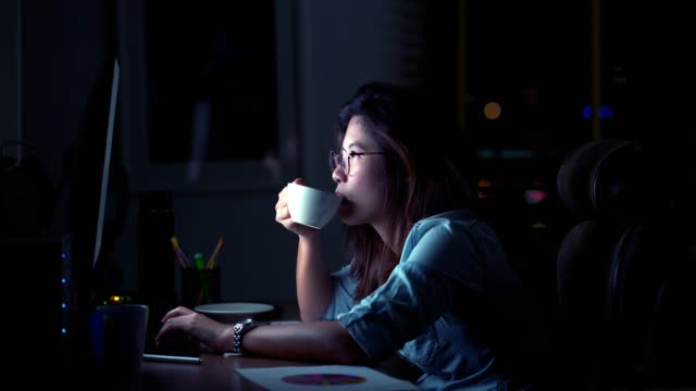 4k footage scene of Attractive Asian woman working late and drinking coffee with serious action on the table in front of computer monitor desktop at workplace in the dark, Work late and Work hard concept