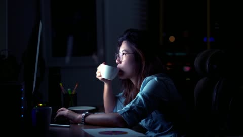 4k footage scene of Attractive Asian woman working late and drinking coffee with serious action on the table in front of computer monitor desktop at workplace in the dark, Work late and Work hard concept Footage scene of Attractive Asian woman working late and drinking coffee with serious action on the table in front of computer monitor desktop at workplace in the dark, Work late and Work hard concept, 4k clip one person stock videos & royalty-free footage