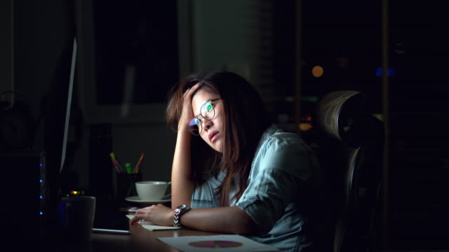4k footage scene of attractive asian woman working late and thinking with serious action on the table in front of computer monitor desktop at workplace in the dark, work late and work hard concept - irriducibilità video stock e b–roll