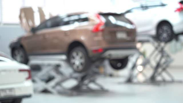 4k footage szene von verschwommenen hintergrund von auto angehoben in automobil-service, transport und wartung auto konzept - wohngebäude innenansicht stock-videos und b-roll-filmmaterial