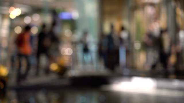 vídeos de stock e filmes b-roll de 4k footage scene of blurred defocused people walking at night time with department store bokeh light background, background and entertainment concept - office background