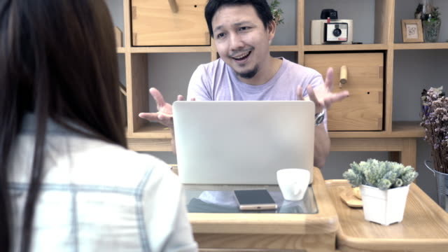 4k footage scene of businessman in casual suit sitting and complaining to rear view of businesswoman about work with technology laptop in modern co-working space, couple and colleague concept