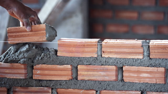 4k footage scene of Closeup hand professional construction worker laying bricks in new industrial site, Construct industry and masonry concept