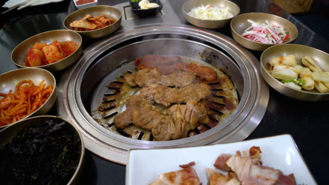 4k footage scene of grilling pork on charcoal grill pan with side dishes traditional korean food, korean style and barbecue concept - cultura coreana video stock e b–roll