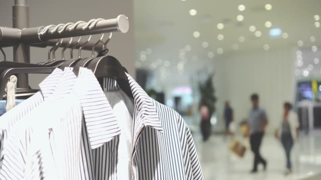 4k footage scene of hanging clothes rack and rail on clothes hangers and people shopping in fashion clothes shop at department store, Shopping mall and Clothing concept