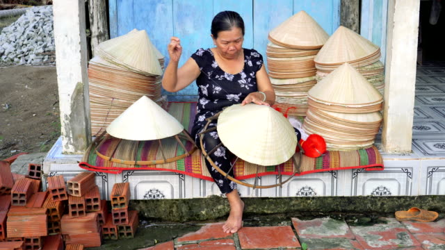 4k footage scene of old vietnamese craftsman making the traditional vietnam hat in the old traditional house in ap thoi phuoc village, cantho province, vietnam, traditional artist concept - prodotto d'artigianato video stock e b–roll