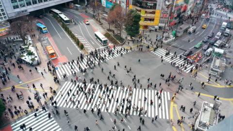 vidéos et rushes de scène d'images 4k des piétons et de la foule de voiture personnes indéfinies marchant au-dessus de l'intersection de rue croisent dans la ville de tokyo de quartier de shibuya, japon. concept japonais de culture et de secteur d'achats - japon