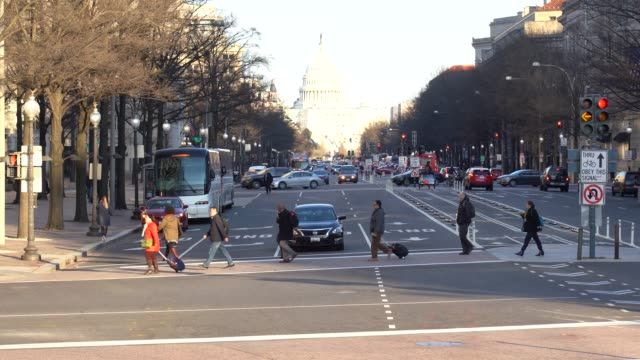 4k footage scene of the united states capitol building with pedestrian and traffic road in rush hour, pennsylvania, capitol hill, washington, d.c., usa, landmark and architecture concept - capitello video stock e b–roll