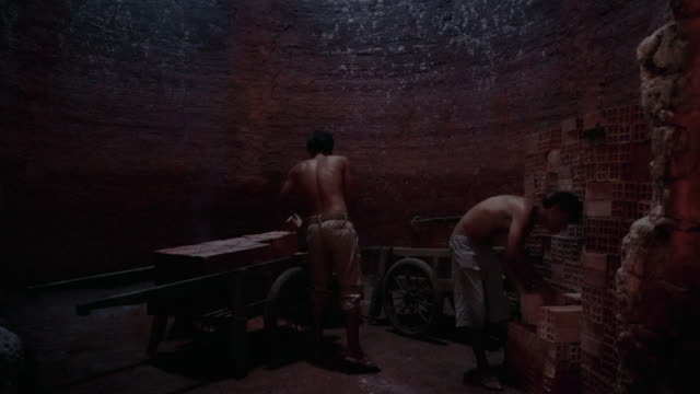 4k footage scene of workers transporting and loading bricks in side of kiln at Mang Thit the land of bricks, Vinh Long province, Vietnam, Culture and Constructure Concept