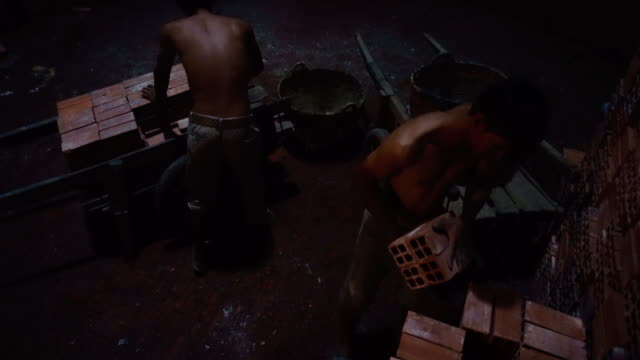 4k footage scene of workers transporting and loading bricks in side of kiln at Mang Thit the land of bricks, Vinh Long province, Vietnam, Culture and Constructeur Concept