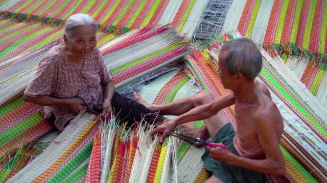 4 k film scen ovanifrån av två vietnamesiska gamla hantverkare att göra och trimning traditionella vietnam mattorna i den gamla traditionella byn på dinh yen, dong thap, vietnam, tradition konstnären koncept - väva bildbanksvideor och videomaterial från bakom kulisserna