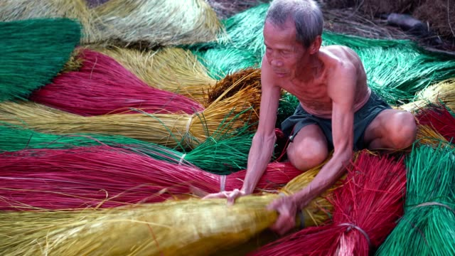 4k footage scene top view of Vietnamese Old craftsman making the traditional vietnam mats in the old traditional village at Dinh Yen, Dong Thap, Vietnam, Tradition artist concept