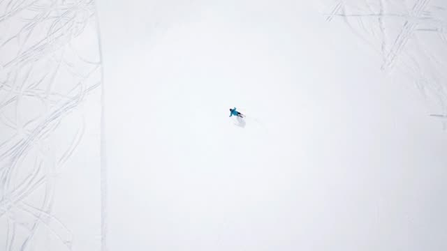 4k footage, top aerial drone view skier skiing on empty ski slope in clouds of snow. Aerial - Top view tracking shot of good alpine skier skiing down the wide ski slope alone. Sunny winter day in Austrian mountains