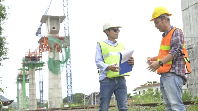 4k footage,Asian civil engineer and specialist Europe civil engineer talking and discusstion about construction of railway in hand holding clipboard ,tablet,walky talky and wearing safety helmet. 4k footage,Asian civil engineer and specialist Europe civil engineer talking and discusstion about construction of railway in hand holding clipboard ,tablet,walky talky and wearing safety helmet. civil engineering stock videos & royalty-free footage