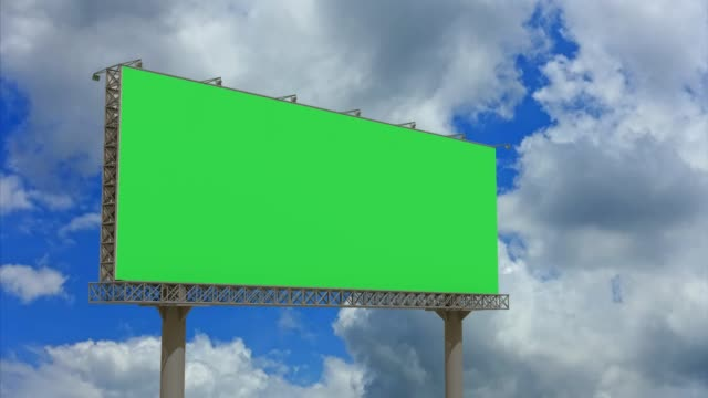 4k footage,empty billboard with chromakey green screen on time lapse cloud and blue sky.advertisement billboard concept. - коммерческий знак стоковые видео и кадры b-roll