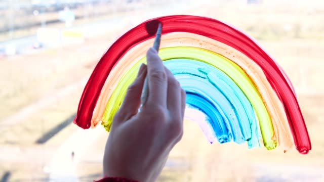 4k. Girl painting rainbow on window during Covid-19 quarantine at home. Stay at home social media campaign for coronavirus prevention, let's all be well, hope. Catch the rainbow
