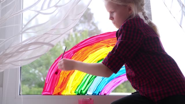 4k. Girl painting rainbow on window during Covid-19 quarantine at home. Stay at home social media campaign for coronavirus prevention, let's all be well, hope. Chase the rainbow