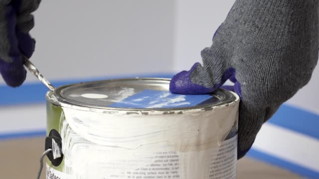4k, gloved hand opening a can of white paint with can opener before starting a paint room. - coperchio video stock e b–roll