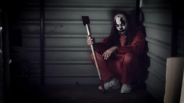 4k halloween horror clown mann mit axt - grauen stock-videos und b-roll-filmmaterial
