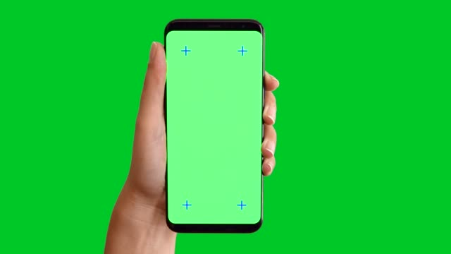 4k hand using smart phone displaying chroma key on green screen